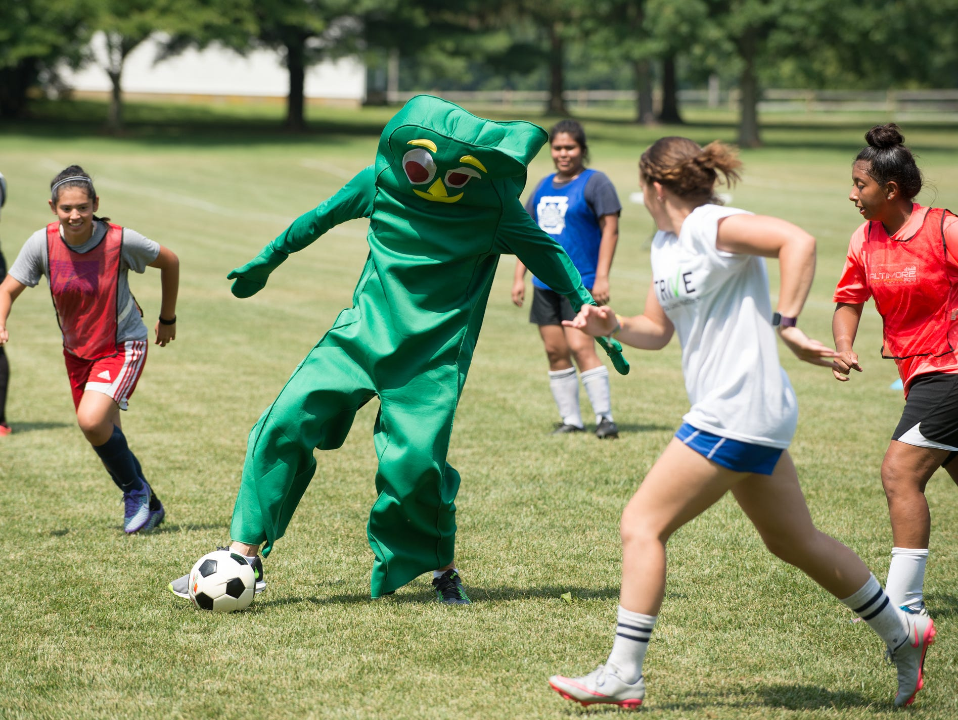 Jeremy Edwards, co-founder of Strive, plays soccer dressed as Gumby at St. Andrew's School in Middletown, Del,.