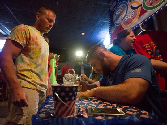 Wrestler Ben Provisor signs autographs for fans during his Olympic Send Off at Rookies Sports Pub in Stevens Point, Thursday, July 28, 2016.