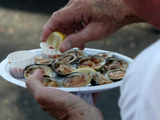 A man adds lemon to his plate of raw oysters at the Red Bank Guinness Oyster Festival in 2014.