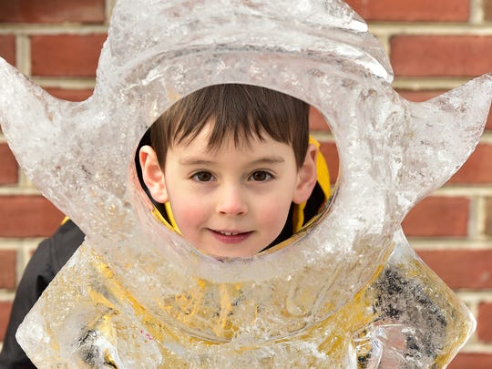Alexander Jackson, 5, looks through an ice sculpture. Crowds are in the Chambersburg downtown area for IceFest on Saturday, evening, January 27, 2018.