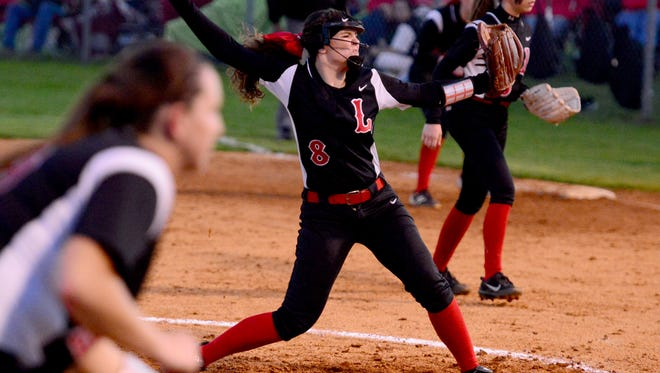 Lexington's pitcher Brylie Brown (8) winds back for a pitch as third baseman Kaitlin Kelley and second baseman Bryleigh Carneal move closer to the batter during their game against South Side, Friday, March 31. Lexington defeated South Side, 5-2.