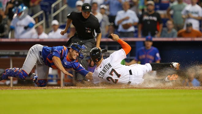 Miami's Giancarlo Stanton, right, slides past the tag from the Mets' Anthony Recker to score the winning run on a sac fly by Marcell Ozuna on Wednesday.