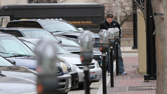 Mike Evans of Mason feeds a parking meter in downtown Cincinnati in 2013.