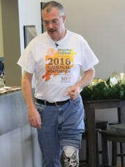 Hartland Township resident Dave Dunville, whose leg was amputated in 2003, practices walking on a new prosthetic ankle he received Thursday.