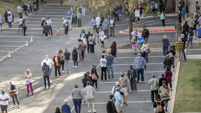 People wait in a long line to vote at a polling place set up at the Renaissance Austin Hotel on Oct. 13, the first day of early voting in Texas.