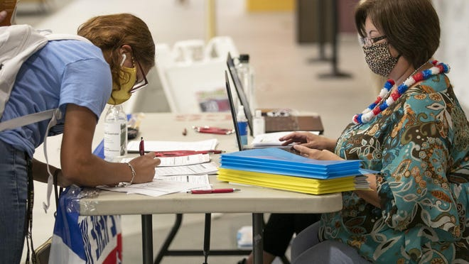 Hays County Chief Voter Registration and Election Clerk Virginia Flores, right, helps student Mariah McBryde, 18, register to vote at Texas State on National Voter Registration Day in September.