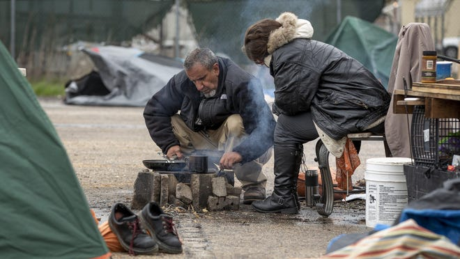 Edward Ybarra and his girlfriend, Missy James, cook potatoes on an open flame at  a state-owned temporary campsite in Southeast Austin on Feb. 20. Austin is expecting freezing or near-freezing overnight temperatures multiple days this week.