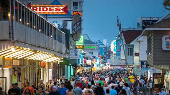 The Boardwalk in Ocean City bustles at night with people moving about and performers entertaining passersby.