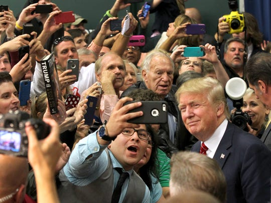 Donald Trump poses for a fan after speaking in 2015
