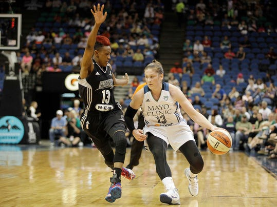 Minnesota Lynx guard Lindsay Whalen (13) pushes the ball down the court against San Antonio Stars guard Danielle Robinson (13) in the first half of a WNBA basketball game on Thursday, July 3, 2014, in Minneapolis. (AP Photo/Stacy Bengs)