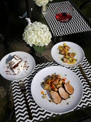 Corie Knopick's table is set with Southwestern pork tenderloin on potato hash, scallops with summer veggies and a ribbon cake for dessert.
