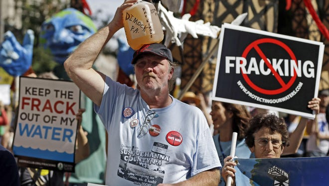 Ray Kemble, of Dimock, Pa., holds a jug of his well water on his head while marching with demonstrators against hydraulic fracturing outside a Marcellus Shale industry conference in Philadelphia in 2012.