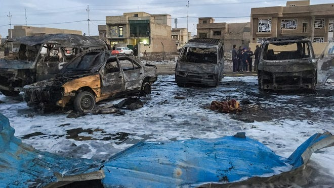 A picture taken with a mobile phone on Feb. 16, 2017 shows burnt vehicles at the scene of a blast by a massive car bomb, which killed dozens in a used car market in southern Baghdad.
