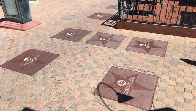 A constellation of star markers in front of the Historic Plaza Theater in downtown Palm Springs. The star markers are part of the Palm Springs Walk of Stars, which honor note-worthy individuals with a connection to Palm Springs.