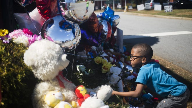 Braylon Woodruff, 5, places balloons Thursday on the memorial outside Townville Elementary School. Thursday was students' first day back to classes after the shooting at the school.