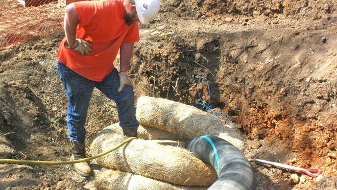 A Forsgren Inc. worker inspects a sewer bypass pump line in 2016, part of sewer upgrades mandated by the Consent Decree.