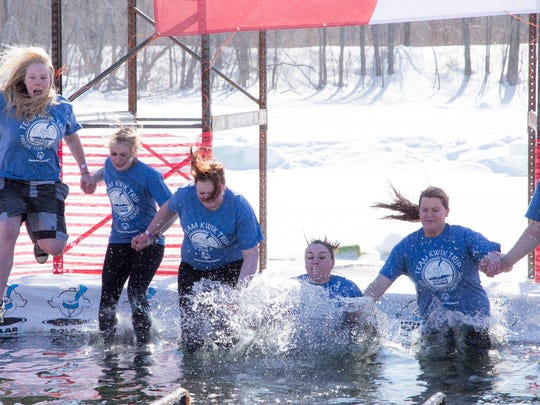 """A group of """"plungers"""" from Team Kwik Trip hold hands for mutual support as they jump into cold water at Sunny Vale Park in Wausau last year."""