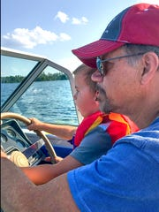 Time at the lake includes time at the wheel for Henry Wood and his grandfather, Douglas Wood.