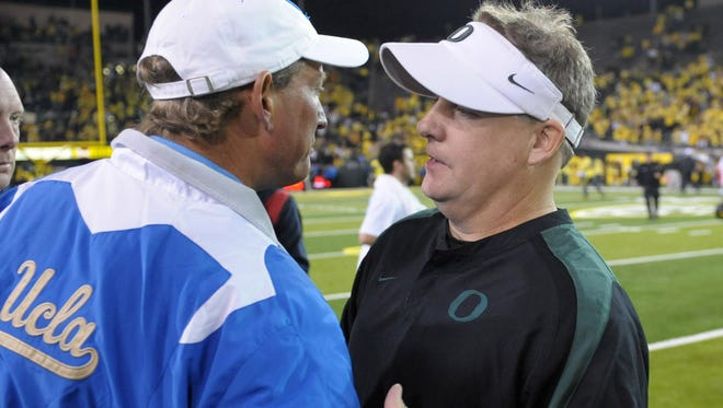 Oregon Ducks coach Chip Kelly (right) shakes hands with UCLA Bruins coach Rick Neuheisel after a 2010 game at Autzen Stadium. Oregon defeated UCLA 60-13.