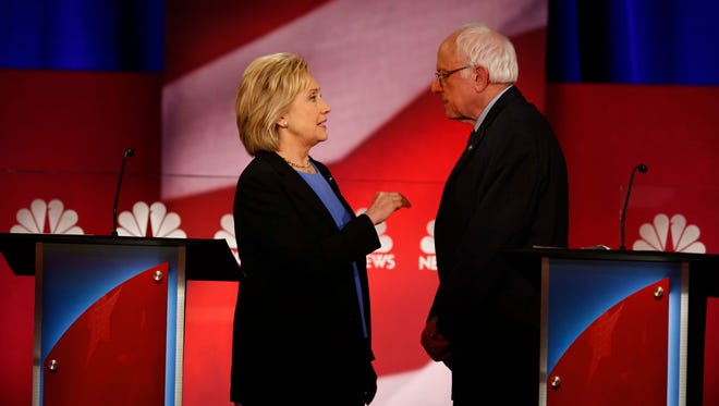 Hillary Clinton and Bernie Sanders speak during a break at the Democratic debate on Jan. 17, 2016, in Charleston, S.C.