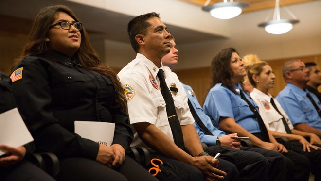 Doña Ana County Firefighter graduates Genesis Dominguez, left, and Jorge Ay III watch a video slide show during a graduation ceremony on Friday, Aug. 26, 2016, for the 15th Doña Ana County Fire and Emergency Services Firefighter Academy.