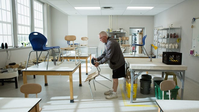 Mark Hartshorne, then principal at Alma d'Arte, takes down chairs from tables in the school's ceramics classroom in January 2017.