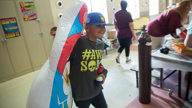 Manny Lopez ,8, grabs a football toss game and carries it across the lunchroom of Tombaugh Elementary School. Manny is suffering from Osteosarcoma, and recently finished ten weeks of chemo therapy. Saturday, February 11, 2017. Manny will soon travling to San Antonio to visit a doctor who will see if his left leg can be saved with out being amputated.