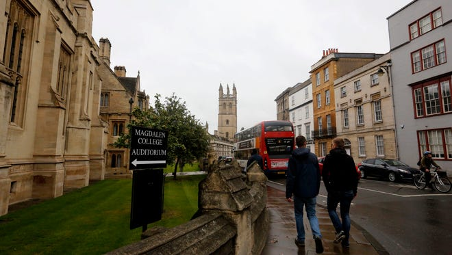 In this Sunday, Sept. 3, 2017 photo, people walk around Oxford University's campus in Oxford, England.
