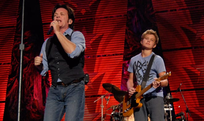 In this 2009 file photo, musician John Mellencamp, left, performs with his band and his son Speck during the Farm Aid Concert in St. Louis.