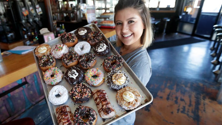 Rachael Cholak holds a tray of specialty doughnuts.