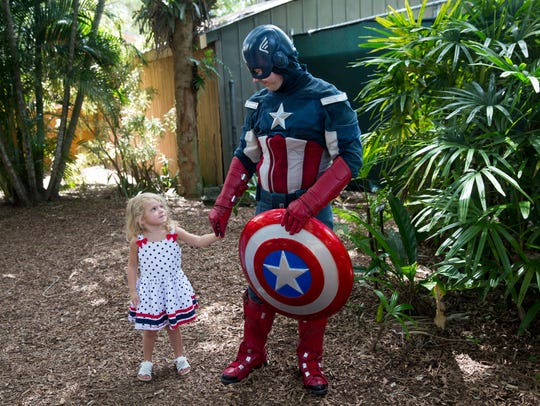 Abigail Biddison, 3, holds hands with Captain America