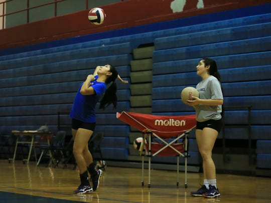 Las Cruces High School volleyball players Amber Saiz, left, and Givy Padilla work on their serves Monday during the first official day of prep volleyball practice in New Mexico.