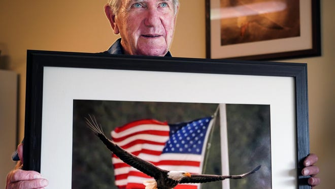Wildlife photographer John Sullivan of Seabrook holds a copy of his bald eagle photo with an American flag, that he has given the staff at Anna Jaques Hospital for all of their medical assistance in helping him recover from COVID-19 this spring.
