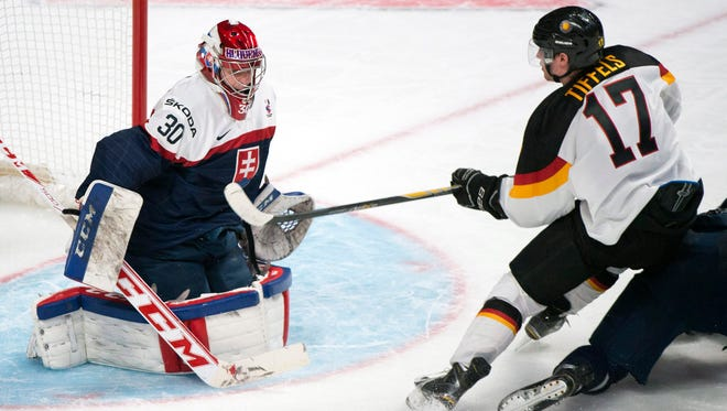 Slovakia's goaltender Denis Godla makes a save against Germany's Frederik Tiffels (17) during the third period of a preliminary round hockey game at the IIHF World Junior Championship in Montreal, Tuesday, Dec. 30, 2014.