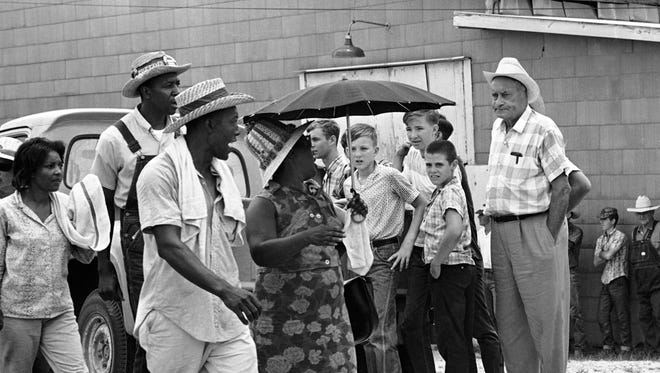 Robert Hicks, vice president of the Bogalusa Voters League, second from left, and other demonstrators shout the Black Power chant as they pass white onlookers upon arrival at Franklinton, Louisiana on July 11, 1966, concluding a two-day march from Bogalusa.