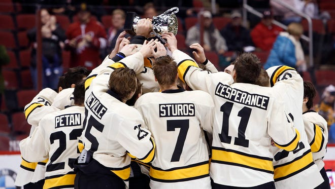 Michigan Tech players hoist the cup after defeating Yale, 2-1, Jan. 10, 2016, in Glendale, Ariz.