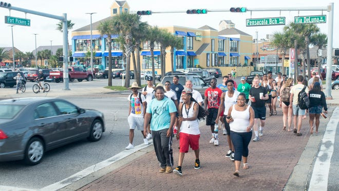 Beach goers cross the street at the intersection of Fort Pickens Road and Pensacola Beach Blvd./Via DeLuna Drive in Pensacola on Monday, February 20, 2017.  Escambia County officials are proposing a traffic roundabout and a pedestrian tunnel at this location to alleviate congestion.