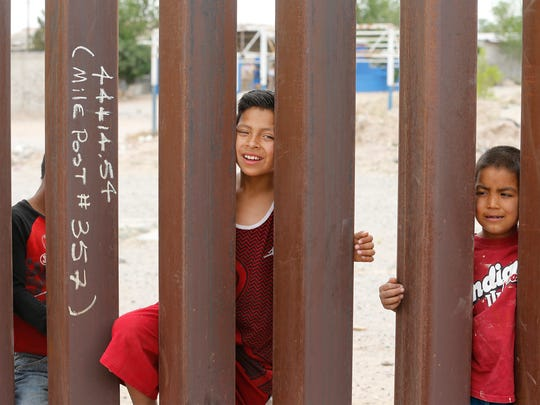 Children from Anapra, Mexico, stand by the new section