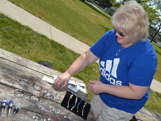 Cindy Millikan lays out some of the items she makes from beach glass, including bracelets and ear rings.