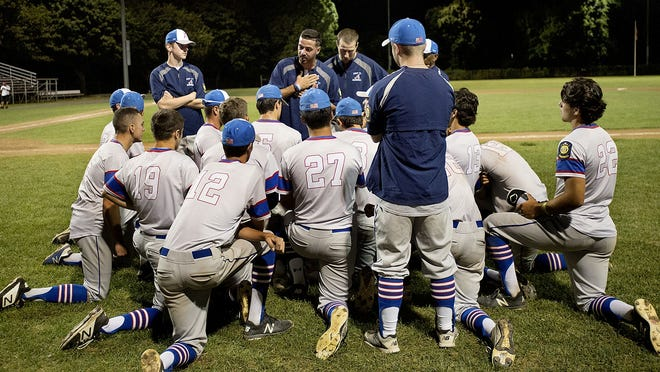 Ashland players take a knee as manager Jake Obid (center) talks to them after a game at Fino Field in Milford last summer.