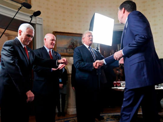 "In this this Jan. 22, 2017, file photo, Vice President Mike Pence, left, and Secret Service Director Joseph Clancy stand as President Donald Trump shakes hands with then-FBI Director James Comey during a reception for inaugural law enforcement officers and first responders in the Blue Room of the White House in Washington. Comey is blasting Trump as ""unethical and untethered to truth,"" and says Trump's leadership of the country is ""ego driven and about personal loyalty."" Comey's comments come in a new book in which he casts Trump as a mafia boss-like figure who sought to blur the line between law enforcement and politics."