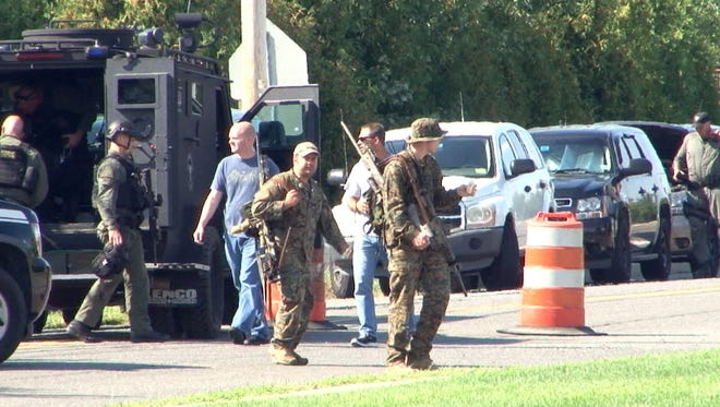 SWAT team members walk across Evergreen Road near the home where a man killed his wife in New Egypt Tuesday, August 25, 2015.  He was taken into custody and transported to Jersey Shore University Medical Center.