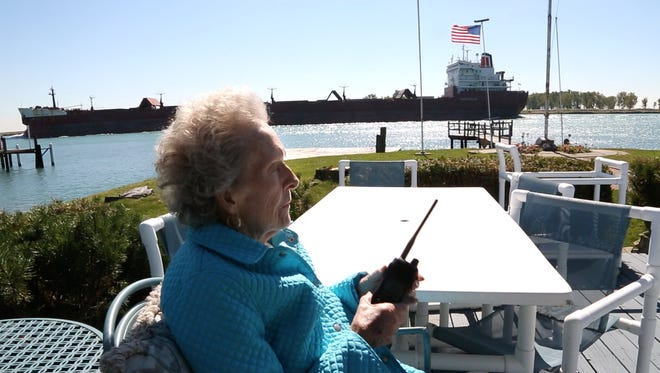 """From her back deck, Arlene Earl, 75 of Harsens Island, Michigan, talks to the passing freighter the """"Indiana Harbor"""" after it had saluted her with a blow of their horn on Tuesday Sept. 23, 2014, on the St. Clair River. Earl, who is known as the """"Flower Lady"""" has been giving flowers to captains of freighters for over 20 years as a thank you to them for saluting Norm LaCroix, her late husbands uncle who would often wave to them. She use to own a flower shop in Southwest Detroit and would take bouquets of flowers down to the J.W. Westcott mailboat to deliver to those passing freighters on the Detroit River."""
