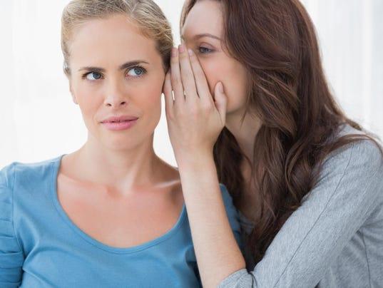 Blond woman hearing a secret from her friend