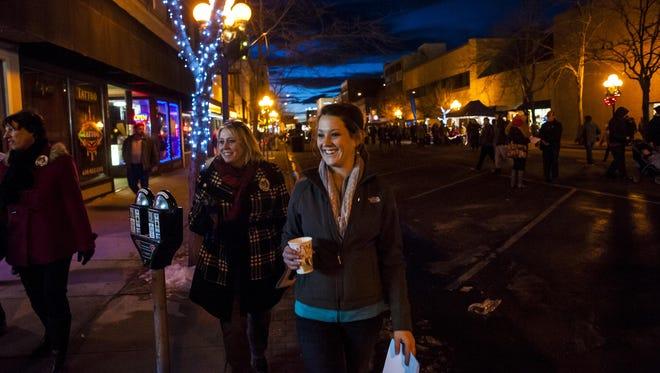 Kellie Pierce walks downtown judging window displays during the Christmas Stroll last year.