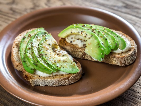 Toasts with tahini sauce and sliced avocado