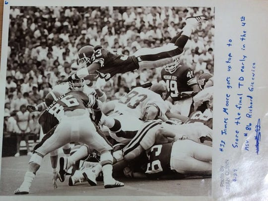 Michigan State fullback James Moore dives over the