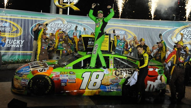 Sprint Cup Series driver Kyle Busch celebrates after winning the Quaker State 400 at Kentucky Speedway.
