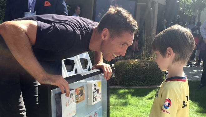 Steve Nash shows his son, Matteo, a gift made by students from Educare Arizona, an early childhood education facility that his charitable foundation helped build in 2010 when Matteo was born.
