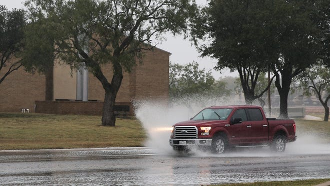 Cars splash up water on the roadway during a rainstorm in San Angelo.